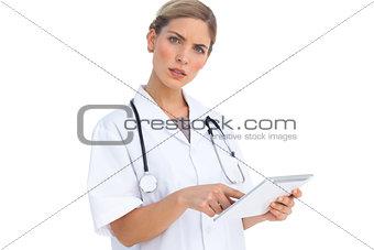 Annoyed nurse using tablet pc