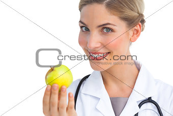 Pretty nurse showing apple to the camera