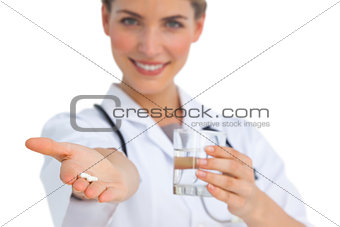 Drugs and water glass held by nurse