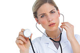 Worried nurse listening to stethoscope