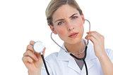 Worried nurse listening to stethoscope