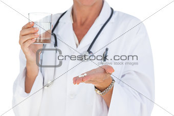 Doctor holding out pills and water glass
