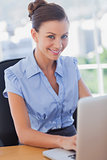 Businesswoman smiling and working on her laptop