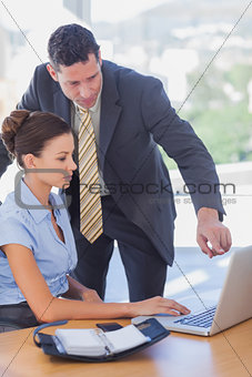 Business people working together on the same laptop