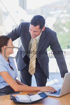Smiling business people working together with a laptop