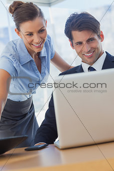 Business people looking the laptop and smiling