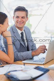 Smiling business people look at each other