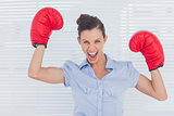 Businesswoman in boxing gloves cheering