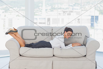 Business woman lying on couch with laptop