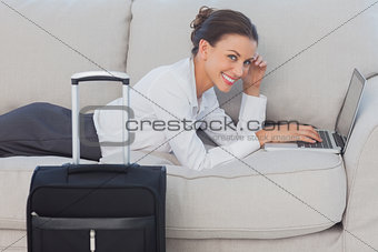 Business woman lying on couch and looking at camera