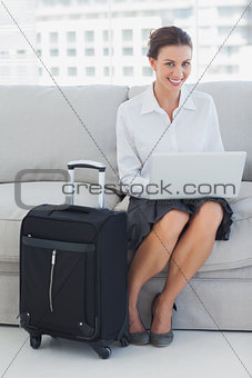 Businesswoman sitting on the couch with laptop