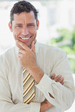 Businessman smiling with hand on chin
