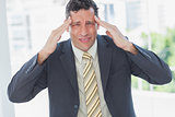 Businessman rubbing his temples and frowning at camera