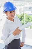 Smiling architect holding plans and wearing hardhat