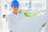 Cheerful architect rolling out a blueprint