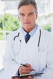 Serious doctor standing with a clipboard
