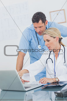 Blonde woman showing something on a laptop to her colleague