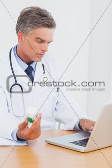 Attractive doctor holding a bottle of pills
