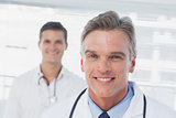 Smiling doctor standing in front of his colleague