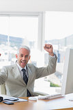 Businessman cheering at his desk