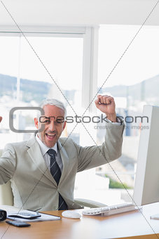 Businessman cheering at his desk