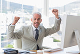 Businessman cheering in his office