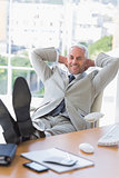 Businessman relaxing at his desk and smiling at camera