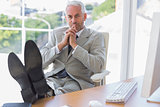 Thoughtful businessman sitting with feet up