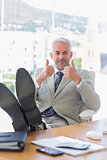 Happy businessman giving thumbs up with feet up