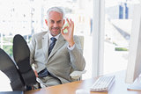 Happy businessman giving ok sign with feet up