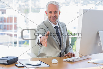 Smiling businessman reaching out arm for handshake