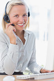 Businesswoman using headset and smiling at camera