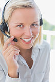 Businesswoman touching headset and smiling at camera