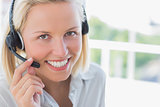 Businesswoman with headset smiling at camera