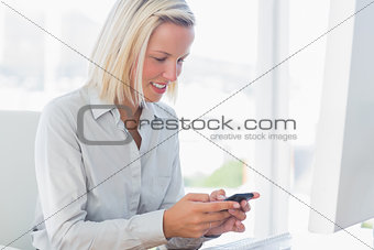 Blonde businesswoman texting