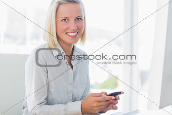 Blonde businesswoman texting and smiling at camera