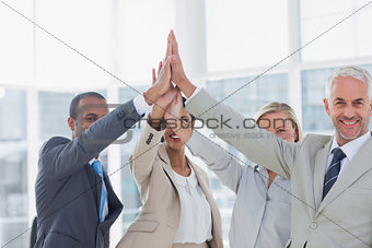 Business team high fiving and smiling at camera