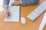 Businessman writing on blank notepad