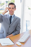 Smiling businessman on the phone looking at camera