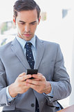 Serious businessman texting on phone