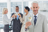 Businessman smiling at camera holding champagne