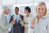 Businesswoman smiling at camera holding champagne