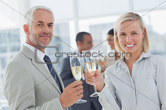 Business team celebrating with champagne and looking at camera