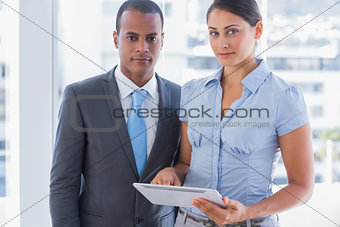 Business team with tablet pc looking at camera