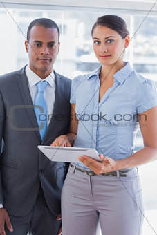Business team with tablet pc smiling at camera