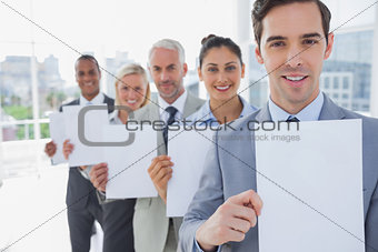 Business team in a line holding blank pages