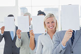 Business team covering face with white paper except for one woman