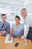 Business people at desk with notepad smiling at camera