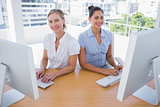 Smiling businesswomen working side by side