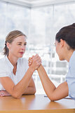 Rival businesswomen having an arm wrestle